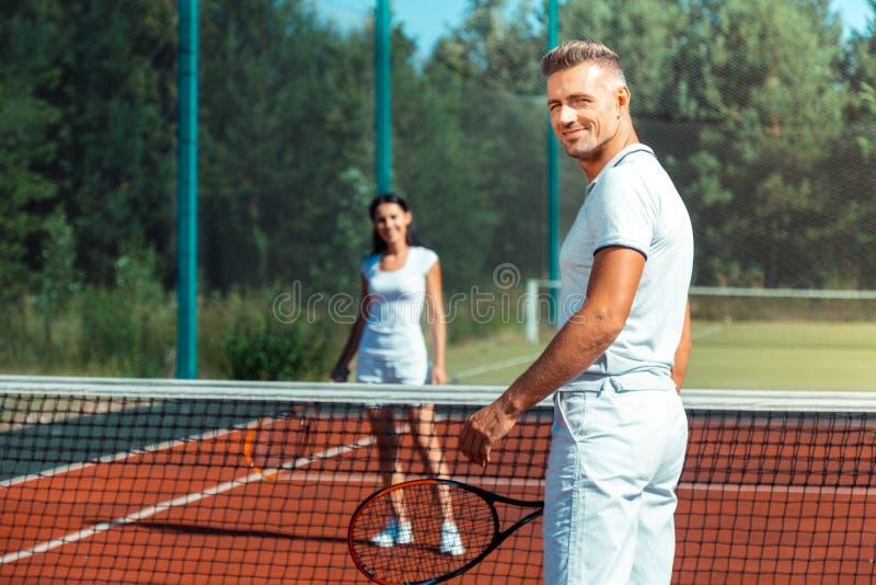 Sensación de emisión del marido que sorprende jugando a tenis con la esposa imagen de archivo