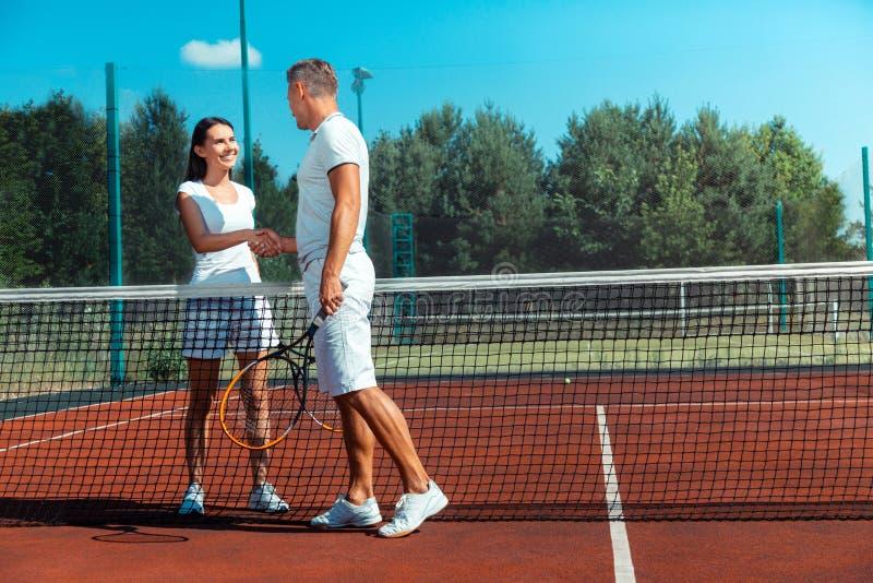 Sensación de emisión de la esposa feliz después de jugar a tenis con el marido imagenes de archivo
