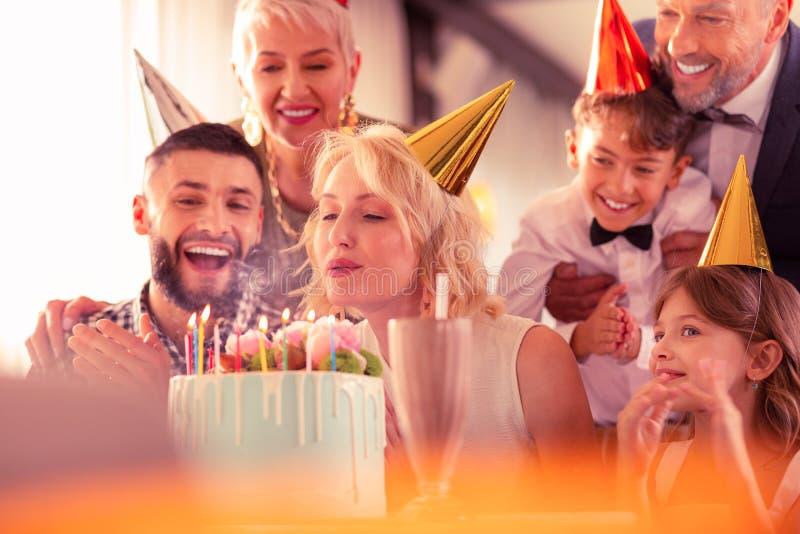 Sensación de la familia emocionada mientras que velas que soplan de la mujer del cumpleaños imagen de archivo