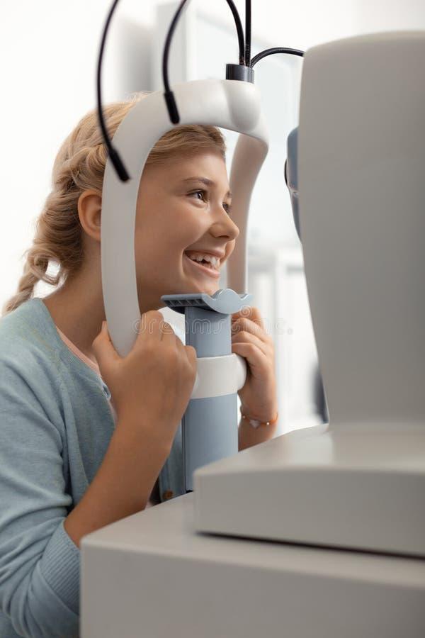 Sensación de la muchacha alegre mientras que teniendo consulta del oftalmólogo foto de archivo