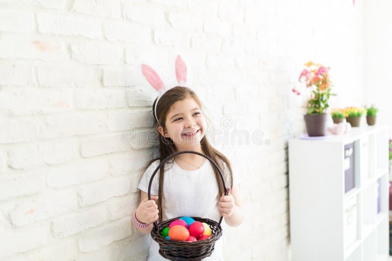 Sensación de la muchacha feliz sobre su colección de Pascua imagen de archivo libre de regalías
