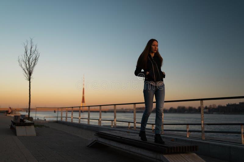 Sensación de la mujer joven confiada durante un paseo de la forma de vida a lo largo del Daugava del río en una puesta del sol fotografía de archivo libre de regalías