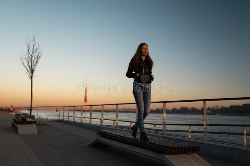 Sensación de la mujer joven confiada durante un paseo de la forma de vida a lo largo del Daugava del río en una puesta del sol fotos de archivo libres de regalías