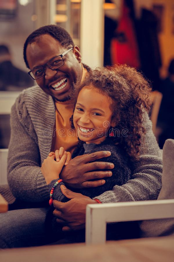 Sensación de ojos oscuros rizada divertida de la muchacha feliz cerca de su padre imagen de archivo