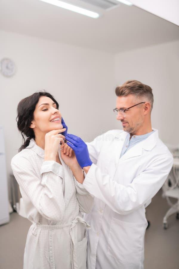 Sensación del cirujano plástico satisfecha con el resultado de la cirugía nasal fotos de archivo