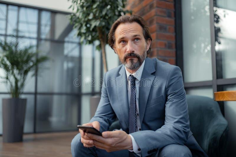 Sensación del hombre de negocios pensativa mientras que espera la reunión imagen de archivo libre de regalías