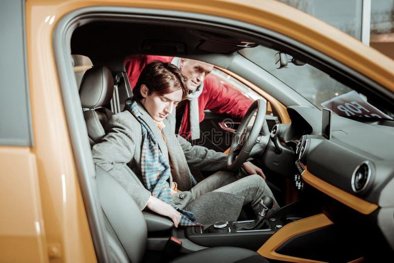 Sensación del padre y del hijo responsable mientras que elige el nuevo coche foto de archivo libre de regalías
