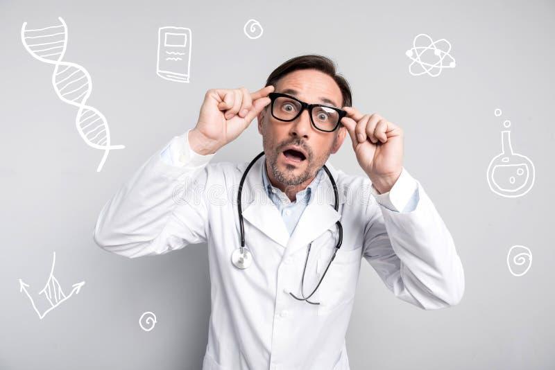 Sensación emocional del doctor sorprendida y abertura su boca imagenes de archivo