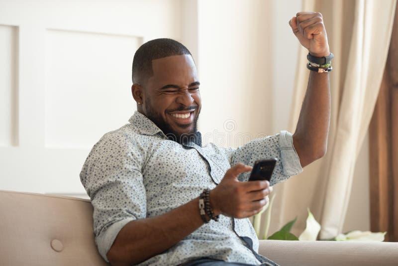 Sensación extática del smartphone de la tenencia del hombre negro eufórica con triunfo móvil foto de archivo