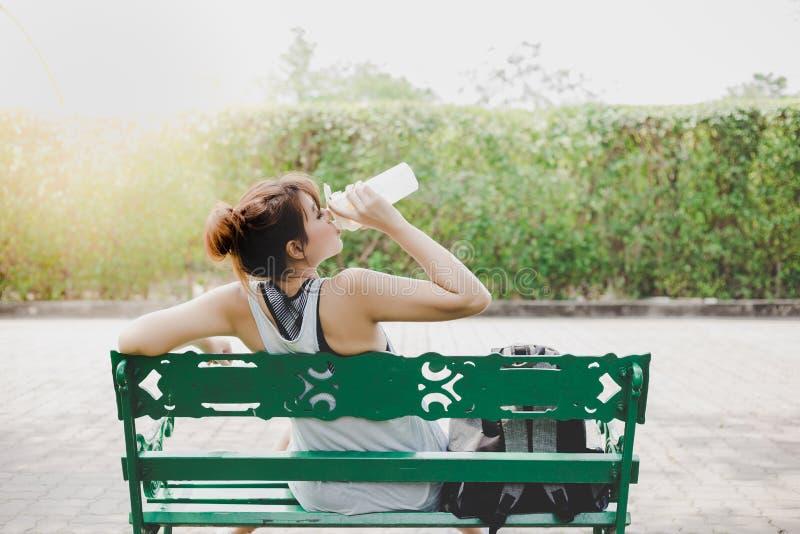 Sensación hermosa de la mujer probada y sedienta, día soleado de los it's La muchacha hermosa encantadora se sienta en banco en fotografía de archivo libre de regalías