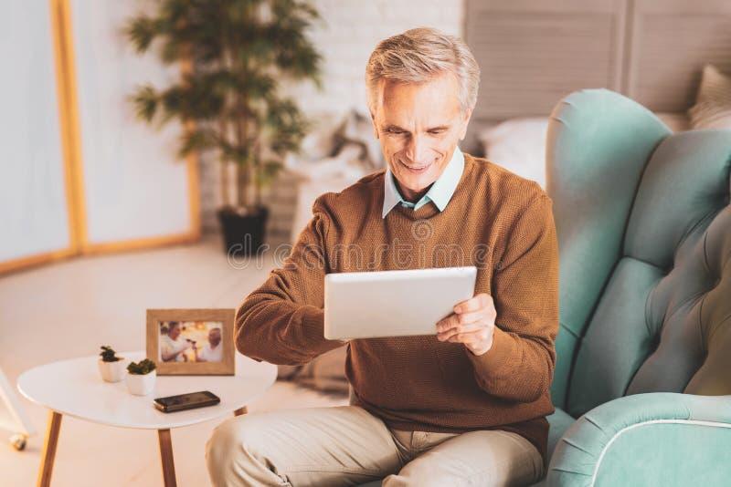 Sensación jubilada del hombre moderna mientras que mira película en la tableta fotografía de archivo