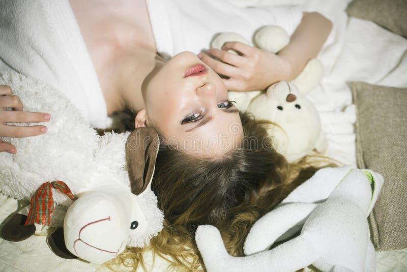 Sensación juguetón La mujer se relaja en cama con los juguetes Mujer joven con los animales suaves Muchacha de la belleza con el  imagenes de archivo