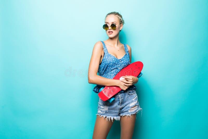 Sensación libre y feliz Mujer joven atractiva en gafas de sol que sonríe y que lleva el monopatín mientras que se opone a backgro fotografía de archivo