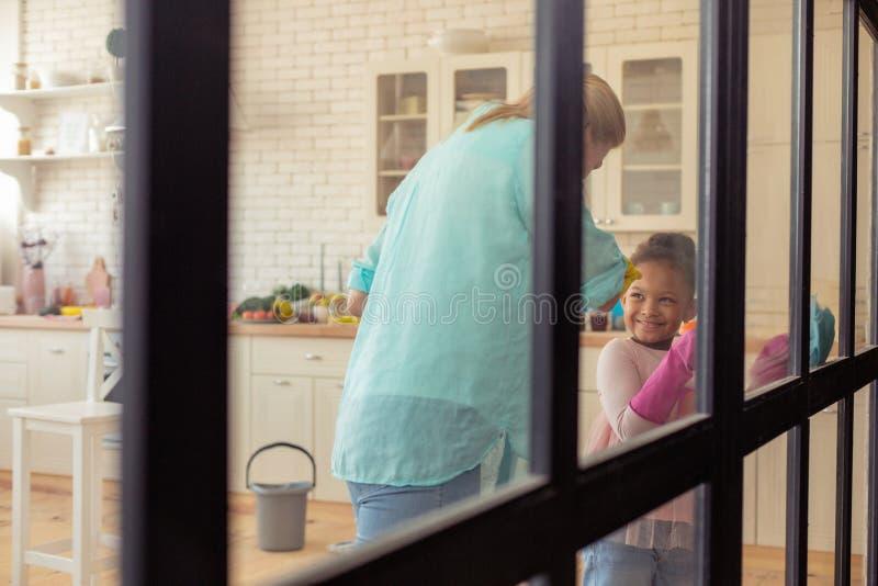 Sensación linda de la muchacha alegre mientras que limpia el apartamento con la madre imagen de archivo libre de regalías
