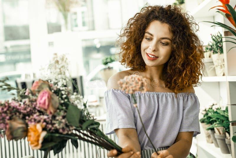 Sensación rizada del florista emocionada mientras que mira las flores rosadas hermosas fotografía de archivo libre de regalías