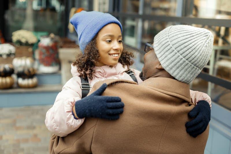 Sensación rizada hermosa de la hija feliz viendo a su padre después de escuela imagenes de archivo
