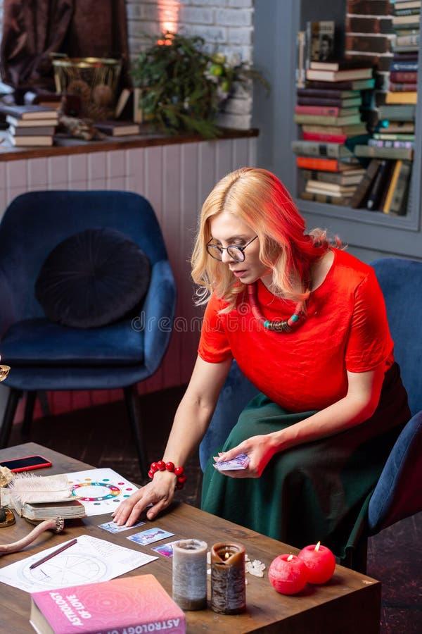 sensación Rubio-cabelluda del astrologist ocupada mientras que lee tarjetas del oráculo fotografía de archivo libre de regalías
