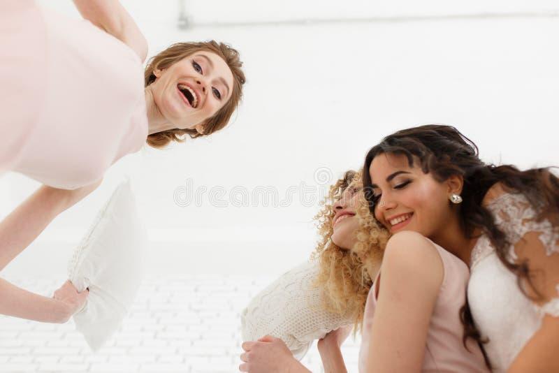 Sensación tan feliz Opinión de debajo de la novia joven atractiva y dos de las damas de honor que hacen caras mientras que toma e imagen de archivo