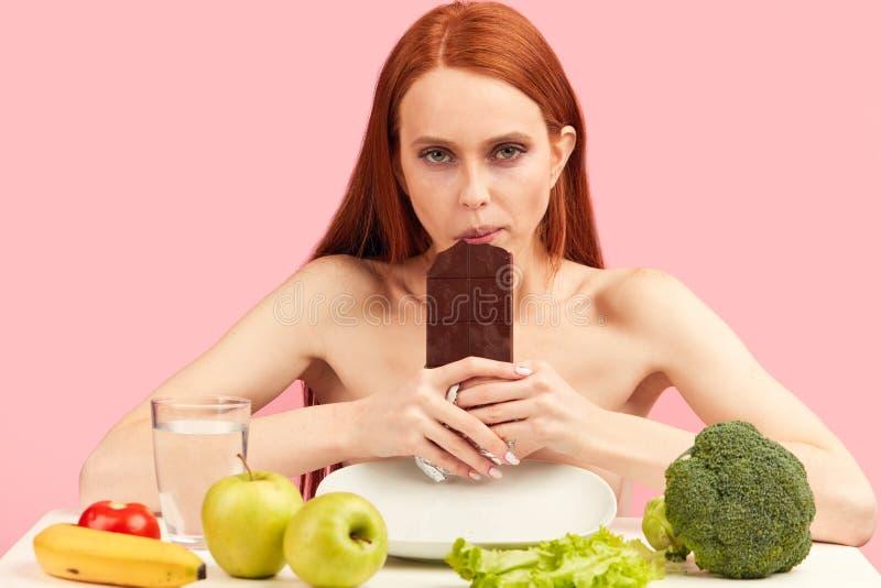 Sensaci?n de la mujer joven triste para comer la barra de chocolate en vez de la comida sana foto de archivo