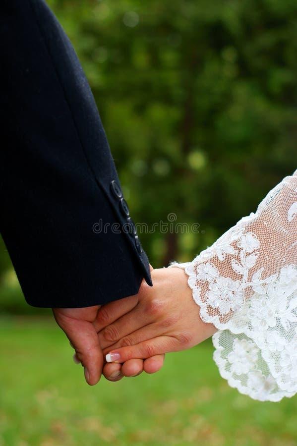 Sensaciones de la boda. Manos de la explotación agrícola de los pares. fotografía de archivo libre de regalías