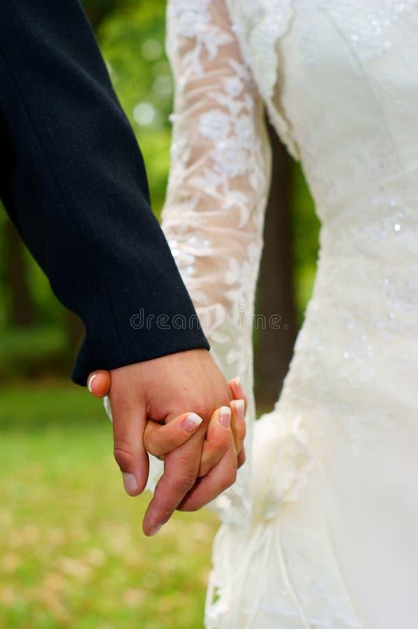 Sensaciones de la boda. Manos de la explotación agrícola de los pares. foto de archivo