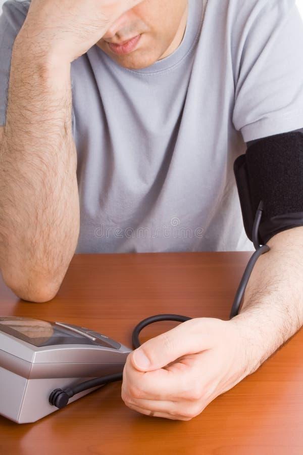 Sensation d'homme en difficulté et contrôlante la tension artérielle photo stock