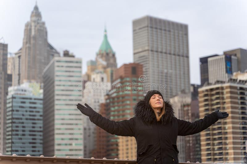Young happy woman with arms raised on the Brooklyn bridge in New York royalty free stock photography