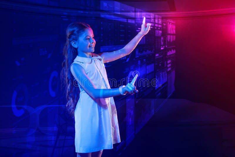 Sensibilità curiosa della ragazza soddisfatta mentre per mezzo di un computer futuristico immagini stock libere da diritti