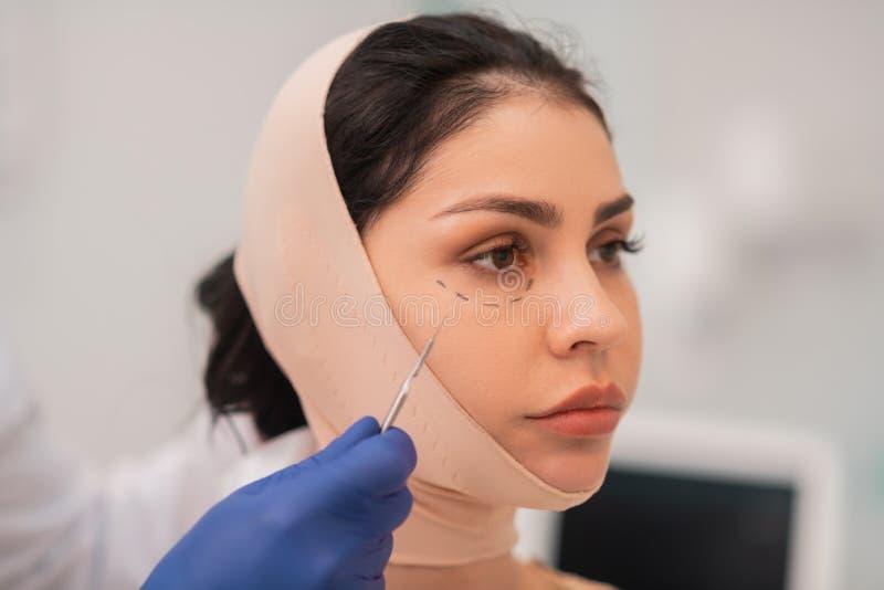 Sensibilità dagli occhi scuri della donna preoccupata prima della chirurgia del fronte immagini stock libere da diritti