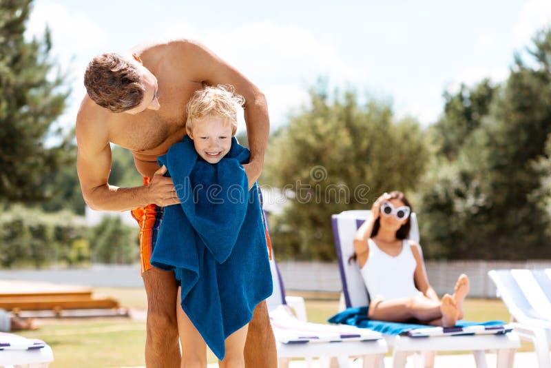 Sensibilità del figlio felice dopo il nuoto mentre stando con l'asciugamano fotografia stock libera da diritti