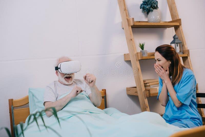 Sensibilità dell'infermiere eccitata circa l'uomo anziano fotografie stock