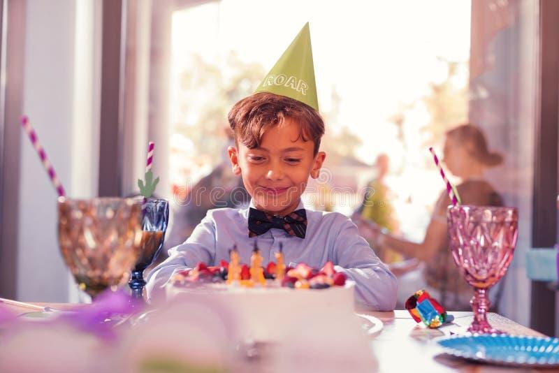 Sensibilità felice del ragazzo soddisfatta mentre esaminando la sua torta di compleanno immagini stock
