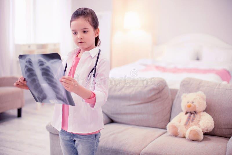 Sensibilità mora della bambina curiosa esaminando i suoi raggi x dei polmoni immagini stock libere da diritti