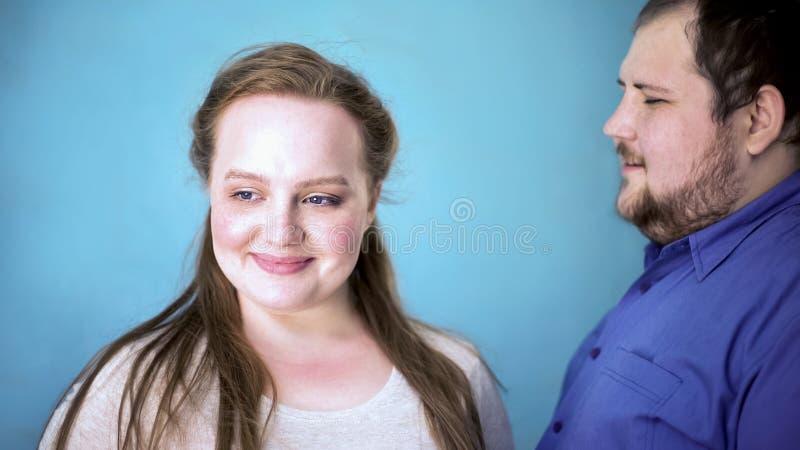 Sensibilità obesa delle coppie felice insieme, relazioni tenere, fondo blu immagini stock libere da diritti