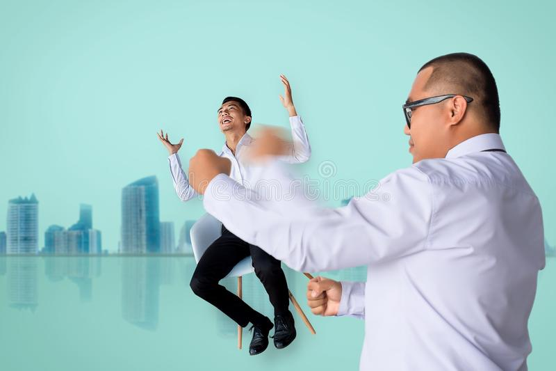 Sensibilità precisa di seduta di perforazione asiatica della sedia dell'uomo di affari dell'uomo di affari in metafora confusade fotografie stock