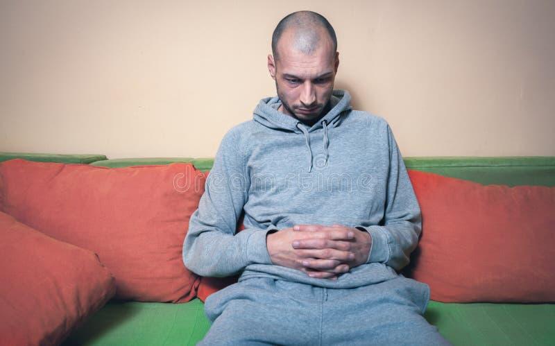 Sensibilità sola e depressa dell'uomo ansiosa e senza ragione per vita che si siede da solo sul suo letto nel suo concentrato sui fotografia stock
