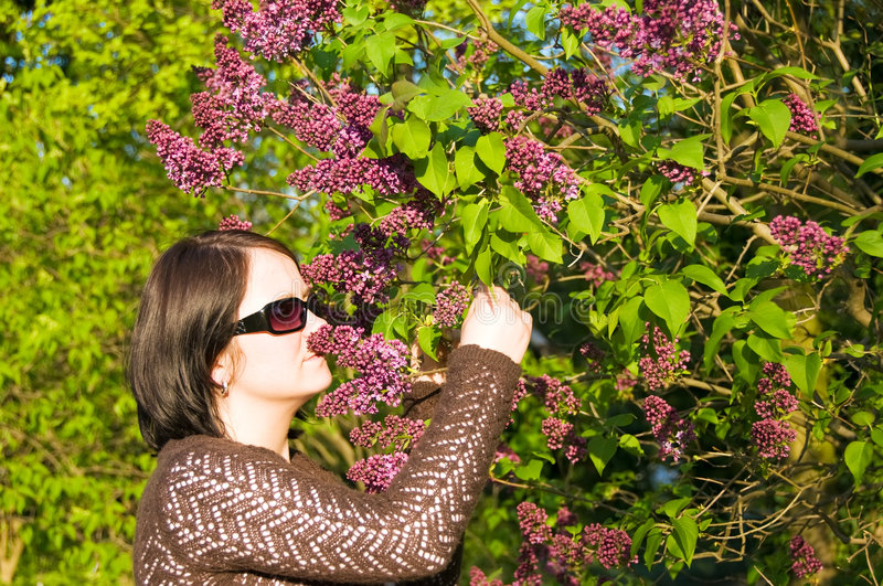 Sensing flavour. Woman is sensing flavour of flower in the park royalty free stock images