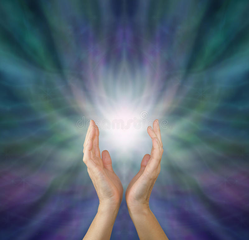 Sensing Healing Energy. Female healing hands reaching up to white light emerging from radiating green and purple ethereal energy formation background with copy stock photos