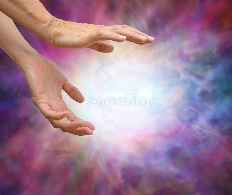 Sensing Reiki Energy. Female hands reaching into energy formation surrounded by an intricate multicolored energy field royalty free stock photography
