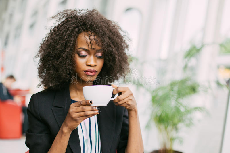 Sensitive close-up portrait of the charming afro-american holding the cup of tea in the cafe. stock photo
