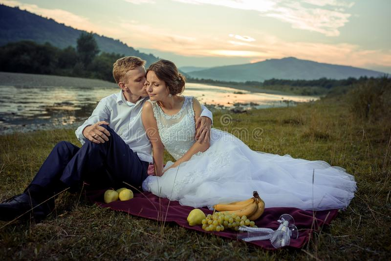 Sensitive portrait of the handsome groom kissing the gorgeous bride in the cheek on the river bank picnic during the stock images