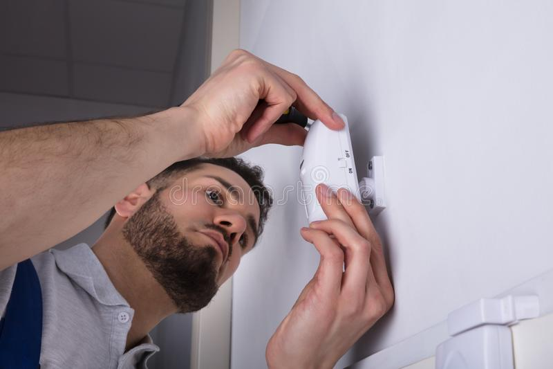 Sensor de la puerta de Installing Security System del electricista en la pared fotografía de archivo