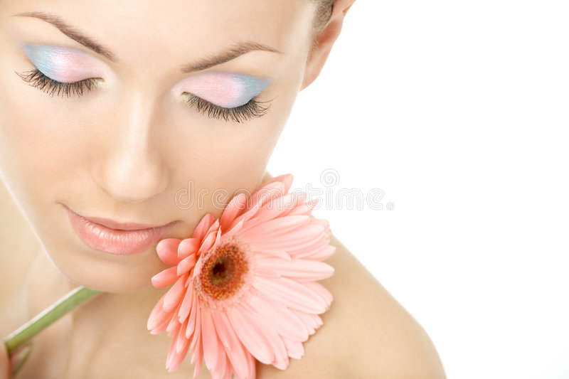 Sensual aroma of a flower. Portrait of the young woman blindly and pink gerbera royalty free stock photography