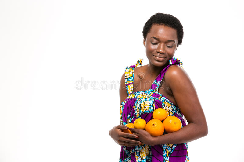 Sensual attractive african woman in bright sundress holding citrus fruits stock photos