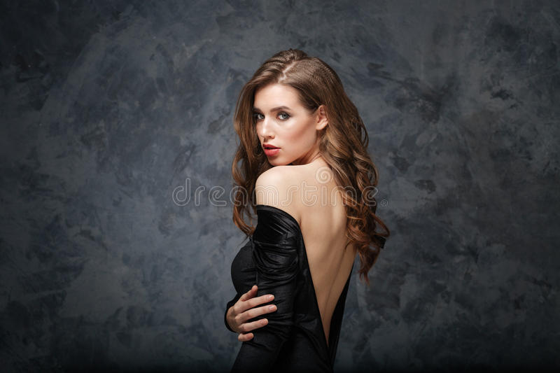 Sensual attractive young woman in classical dress with open back. Over grey background royalty free stock image