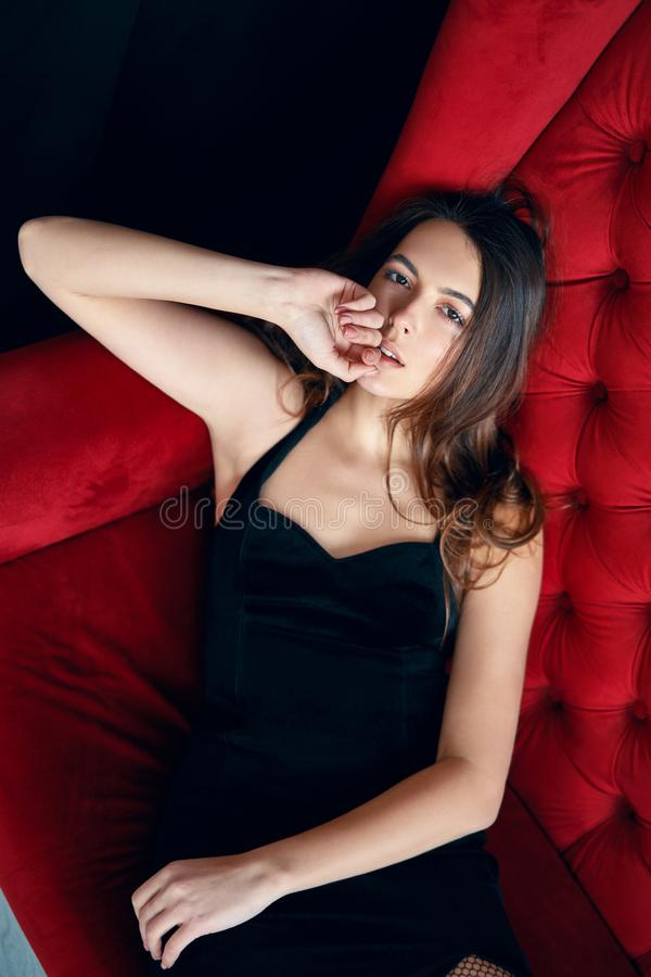 Sensual beautiful woman posing in sexy black dress on red sofa. Female beauty concept royalty free stock images
