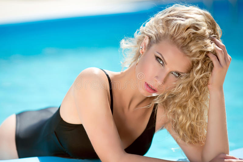Sensual blond woman in blue water swimming pool, model with curl stock photography