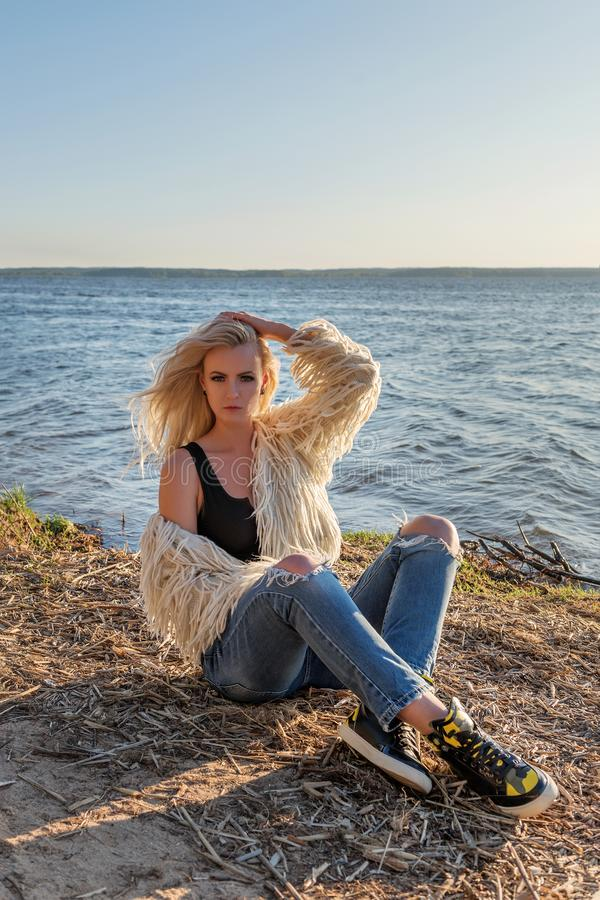 Sensual blonde model woman in modern lifestyle clothing sits on the beach in the rays of the rising sun. Beautiful attractive blonde model woman in modern royalty free stock photo