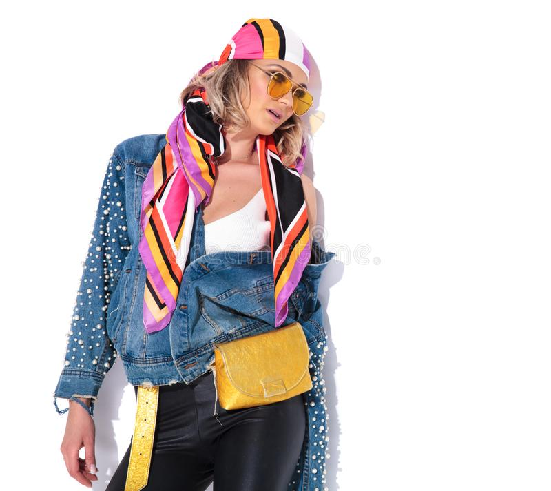Sensual blonde woman with parted lips looks to side. Sensual blonde woman with parted lips and colorful clothes looks to side while standing near a white wall stock images