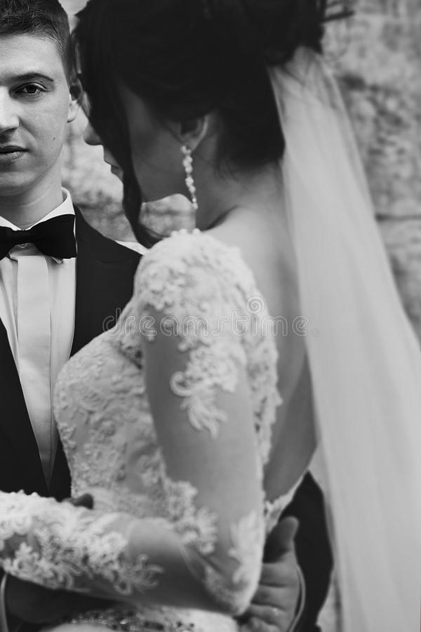 Sensual brunette bride hugging groom in black suit closeup, wall royalty free stock photography